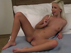 A youthful woman with blond hair is laying nude on a bed. She is holding a magic wand that she wets with her mouth. A tiny later she moves the magic wand over her hooters and then lower down over her cunt before she nails herself with it.