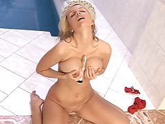 A youthfull ash-blonde lady is sitting nude on the floor next to a swimming pool. She is holding her hard boobs and wringing them. She caresses her beaver for a while and then picks up a hitachi with which she rubs her entire body.